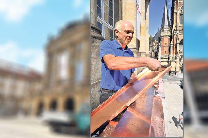 Klempner-Meister Thomas Friedrich zeigt die neue Kupferabdeckung, die den Regen von der Balkonfassade abweisen soll.