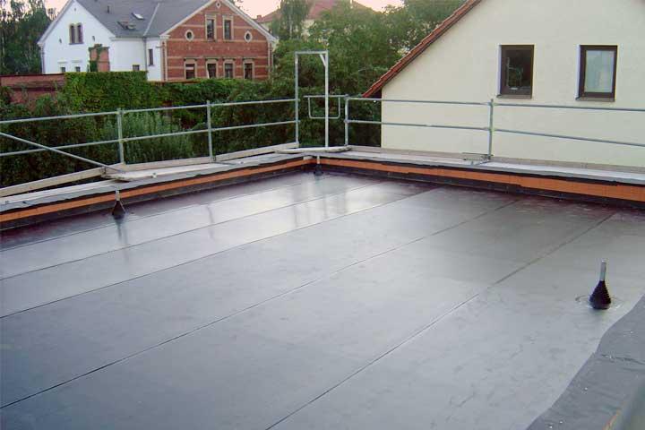 Flachdachabdichtung in Dresden mit Polyfin Kunststoff Dach- und Dichtungsbahn  (ECB) auf Dampfsperre und Gefälledämmung, Befestigung durch Auflast (Kies 16/32) einschließlich der Entwässerung und Verblechung